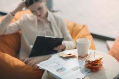 Biznesowe mapy i notatki na stole i bizneswomanie pracuje behind obraz royalty free