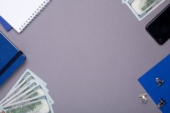 Biznesowe rzeczy pieniądze, błękitny notatnik i telefon komórkowy na szarym tle -, obraz royalty free