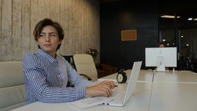 Biznesowego życia pojęcie Żeńskiego pracownika młodzi biurowi spojrzenia przy okno z przykrością podczas gdy pisać na maszynie na zdjęcie wideo