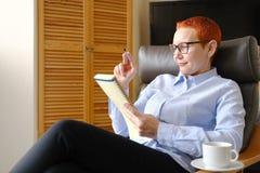 biznesowego krzesła siedząca kobieta Atrakcyjny młody bizneswomanu obsiadanie w krześle, patrzeje dokumenty Napój kawa obraz royalty free