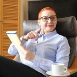 biznesowego krzesła siedząca kobieta Atrakcyjny młody bizneswomanu obsiadanie w krześle, patrzeje dokumenty Napój kawa zdjęcie stock