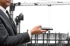 Biznesowego mężczyzna chwyta mądrze telefon z budowa żurawiem Zdjęcie Stock