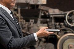 Biznesowego mężczyzna chwyta mądrze telefon z maszyną Fotografia Royalty Free
