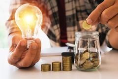 Biznesowego mężczyzna kładzenia moneta w szklanej butelki oszczędzania banku i accoun obraz royalty free