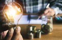 Biznesowego mężczyzna kładzenia moneta w szklanej butelki oszczędzania banku i accoun fotografia royalty free