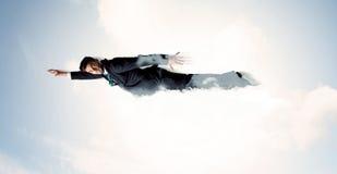 Biznesowego mężczyzna latanie jak bohater w chmurach na niebie obraz stock