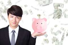 Biznesowego mężczyzna mienia menchii prosiątka bank Fotografia Stock