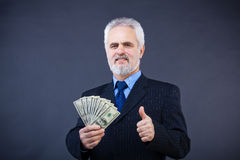 Biznesowego mężczyzna mienie gotówkowy i seans aprobaty Fotografia Stock