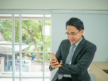 Biznesowego mężczyzna obsiadanie na jego dysku i sprawdza jego telefon komórkowego obrazy stock