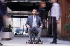 Biznesowego mężczyzna obsiadanie w biurowym krześle, ludzie grupuje omijanie obok Zdjęcie Stock