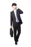 Biznesowego mężczyzna odprowadzenie i obcojęzyczny telefon komórkowy Zdjęcia Stock