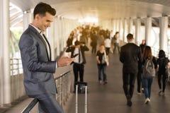 Biznesowego mężczyzna podróżnego use mądrze telefon na spaceru sposobie z wroną Zdjęcia Stock