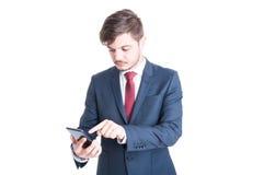 Biznesowego mężczyzna pozycja wyszukuje smartphone Obrazy Stock
