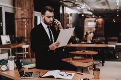 biznesowego mężczyzna s kostium patrzeje paperwork Opowiadać na telefonie obraz royalty free