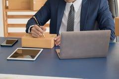 Biznesowego mężczyzna writing adres na pakunku SME zaczynają up Zdjęcie Stock