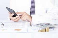Biznesowego mężczyzna wzruszający telefon komórkowy z czeków dane repot dokument o zdjęcie royalty free