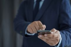 Biznesowego mężczyzny chwyt smartphone na ulicie i kopia interliniuje obraz royalty free