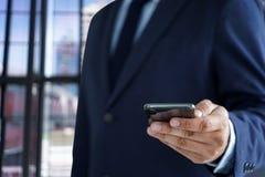 Biznesowego mężczyzny chwyt smartphone na ulicie i kopia interliniuje obrazy royalty free