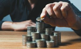 Biznesowego mężczyzny kładzenia moneta na stosie pieniądze oszczędzania bank i accou obraz stock