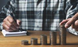 Biznesowego mężczyzny kładzenia moneta na stosie pieniądze oszczędzania bank i accou obraz royalty free