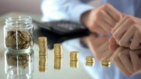 Biznesowego mężczyzny kładzenia sterta monety w jeden rząd, wzrastający zysk, finanse zdjęcie stock