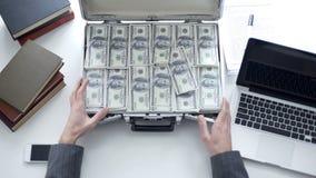 Biznesowego mężczyzny otwarcia skrzynka pełno pieniądze, zapłata dla osoby wtajemniczonej informacji zdjęcia stock