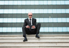 Biznesowego mężczyzna spojrzenia ufna używa komputerowa pastylka Fotografia Stock