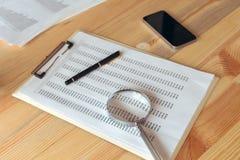 Biznesowego raportu analiza, powiększa - szkło nad papierowym spreadsheet zdjęcie stock