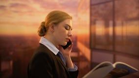Biznesowej damy piękna czytelniczy magazyn i dzwonić przyjaciel podczas gdy odpoczywający przy biurem zdjęcie wideo