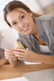 Biznesowej kobiety łasowania kanapka przy pracą Obrazy Royalty Free