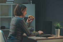 Biznesowej kobiety łasowanie piec przekąskę nad biurowym laptopem Obraz Royalty Free