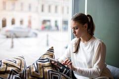 Biznesowej kobiety czytelniczy ebook na dotyka ochraniaczu podczas czasu wolnego w kawiarni zdjęcie royalty free