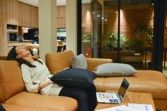 Biznesowej kobiety dosypianie na kanapie w żywym pokoju przy nocą Obrazy Stock