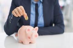 Biznesowej kobiety kładzenia moneta w prosiątko banka Fotografia Royalty Free