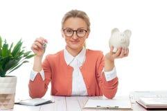 Biznesowej kobiety lub agenta nieruchomości mienia klucze i prosiątko bank Fotografia Stock