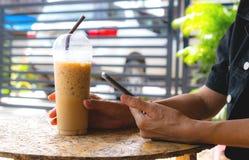 Biznesowej kobiety mienia zimna kawa i smartphone sprawdza dane zdjęcie stock