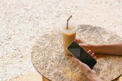 Biznesowej kobiety mienia zimna kawa i smartphone sprawdza dane obrazy stock