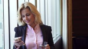 Biznesowej kobiety napoje nawadniają i spojrzenia przy fotografiami w ona telefon zbiory wideo