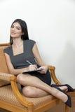 Biznesowej kobiety obsiadanie na ręki krześle zdjęcie royalty free