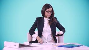Biznesowej kobiety obsiadanie przy biurkiem w biurowym i uśmiechniętym Za błękitnym tłem Ona ` s opowiada na telefonie na zbiory wideo