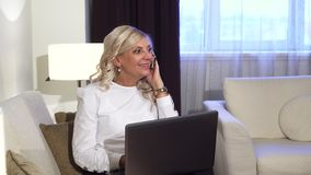 Biznesowej kobiety obsiadanie przy laptopem i brać ona wezwanie zdjęcia stock