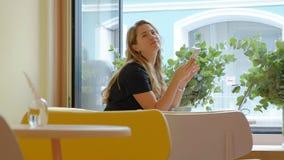 Biznesowej kobiety obsiadanie przy stołem w cukiernianym pije działaniu na laptopie i kawie zbiory