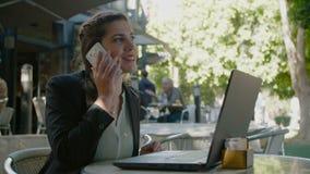 Biznesowej kobiety obsiadanie w kawiarni pracuje na laptopie i robi rozmowom telefonicza, zbiory