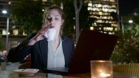 Biznesowej kobiety obsiadanie w kawiarni przy nocą pracuje na laptopie i robi rozmowom telefonicza, zbiory