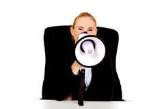 Biznesowej kobiety obsiadanie za biurkiem i krzyczeć przez megafonu Zdjęcia Royalty Free