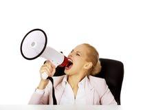 Biznesowej kobiety obsiadanie za biurkiem i krzyczeć przez megafonu Zdjęcia Stock