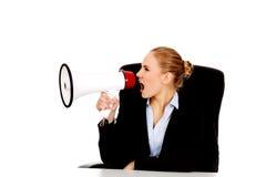 Biznesowej kobiety obsiadanie za biurkiem i krzyczeć przez megafonu Fotografia Stock