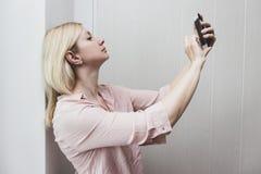 Biznesowej kobiety pozycja blisko robić selfie i ściany zdjęcie royalty free
