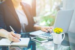 Biznesowej kobiety ręka pisze notatniku z piórem i używa a zdjęcia stock