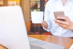 Biznesowej kobiety ręka trzyma telefon komórkowego i filiżankę kawy wewnątrz zdjęcie royalty free